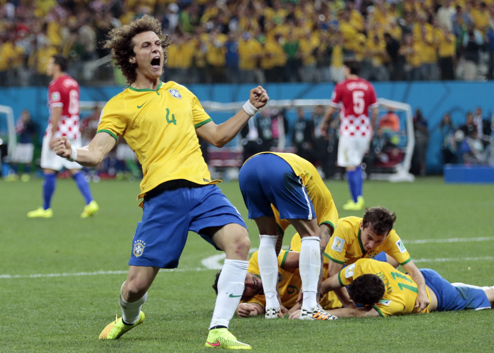 Brazil's David Luiz (4) celebrates teammate Oscar's (11) goal during the group A World Cup soccer match between Brazil and Croatia, the opening game of the tournament, in the Itaquerao Stadium in Sao Paulo, Brazil, Thursday, June 12, 2014.