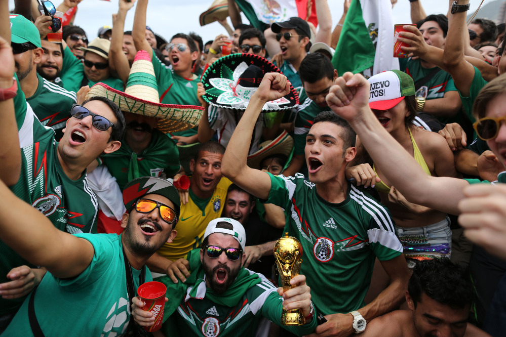 Mexico soccer fans celebrate their team's 1-0 victory over Cameroon at a World Cup match, inside the FIFA Fan fest area on Copacabana beach in Rio de Janeiro, Brazil, Friday, June 13, 2014.