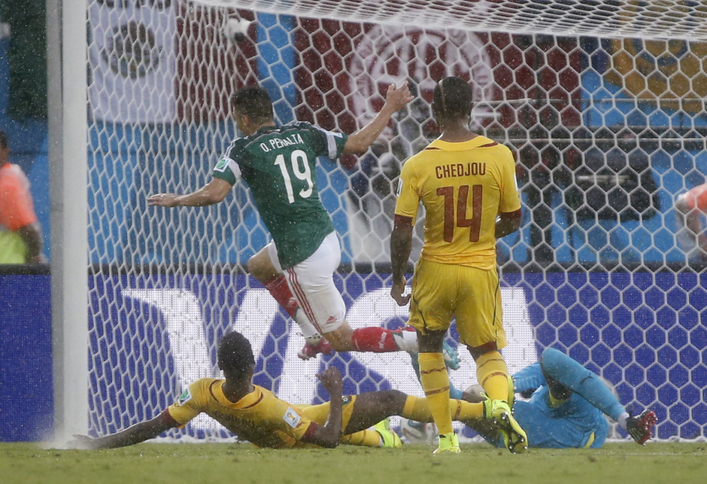 Mexico's Oribe Peralta, centre, scores the opening goal during the group A World Cup soccer match between Mexico and Cameroon in the Arena das Dunas in Natal, Brazil, Friday, June 13, 2014.