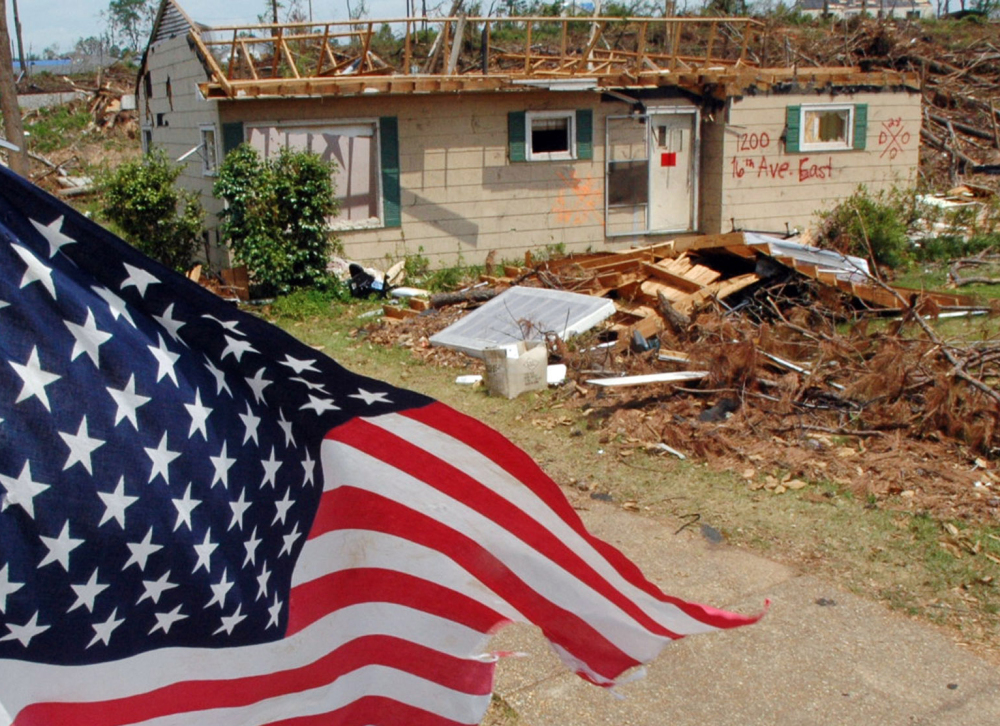 A flag flies over the remains of a tornado-ravaged neighborhood in Tuscaloosa, Ala., in 2001. Oklahoma and Kansas may have the reputation as tornado hot spots, but Florida and the rest of the Southeast are far more vulnerable to deadly twisters, a new analysis shows.