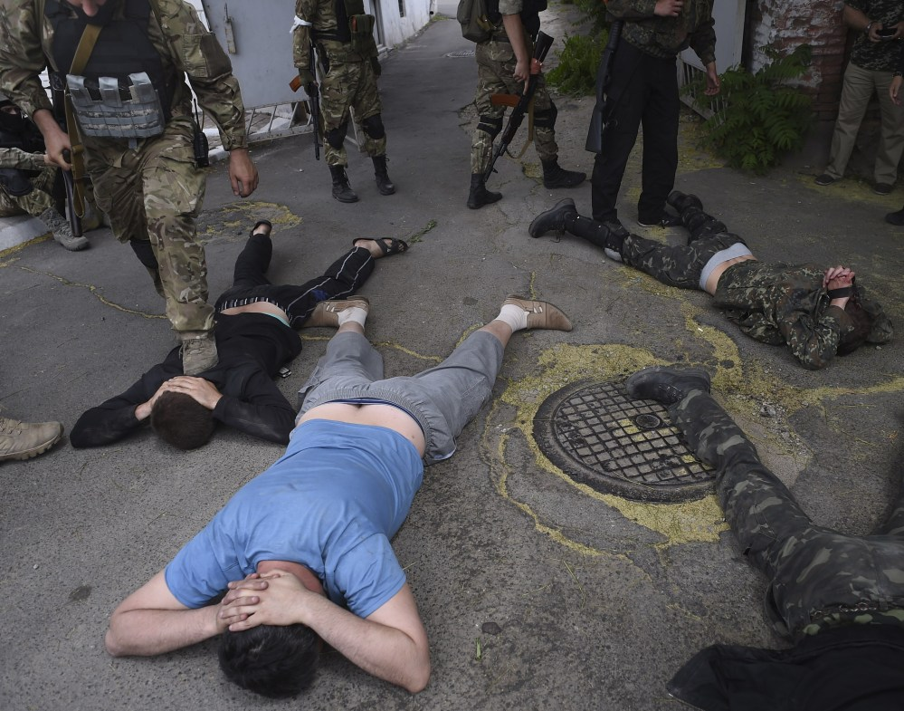 Ukrainian troops from battalion Azov ground men detained at the site of a battle with pro-Russian separatists in Mariupol, eastern Ukraine, on Friday.