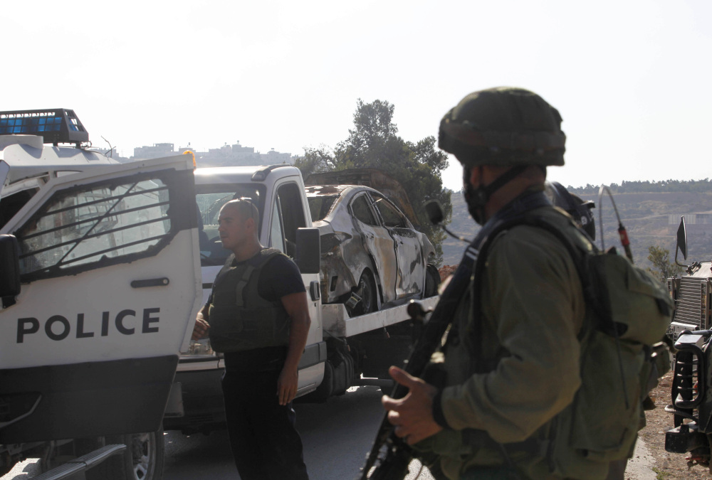 Israeli soldiers transport a burned-out car Friday that is reportedly connected to the disappearance of three teenage settlers near the West Bank city of Hebron. The three left their religious seminary Thursday night and have not been seen since.