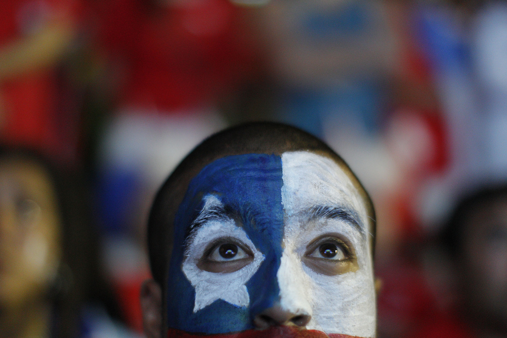 A soccer fan with his face painted to represent the Chilean national flag, watches the live broadcast of the World Cup match between Chile and Australia, inside the FIFA Fan Fest area on Copacabana beach in Rio de Janeiro, Brazil, Friday, June 13, 2014. Chile went on to defeat Australia 3-1 in the group B game at the Arena Pantanal in Cuiaba.