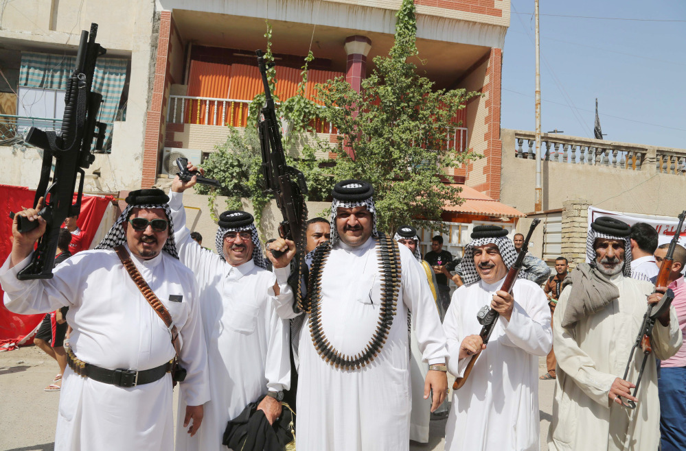 Iraqi Shiite tribal fighters pose with their weapons in Baghdad's Sadr city, Iraq, Saturday, June 14, 2014, after authorities urged Iraqis to help battle insurgents. Hundreds of young Iraqi men gripped by religious and nationalistic fervor streamed into volunteer centers across Baghdad Saturday, answering a call by the country's top Shiite cleric to join the fight against Sunni militants advancing in the north. (AP Photo/Karim Kadim) Iraqi Shiite tribal fighters pose with their weapons in Baghdad's Sadr city, Iraq, on Saturday after authorities urged Iraqis to help battle insurgents.