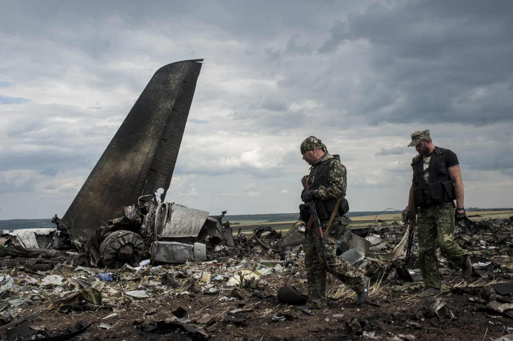 Pro-Russian fighters walk by the site of remnants of a downed Ukrainian army aircraft Il-76 at the airport near Luhansk, Ukraine, on Saturday. Pro-Russia separatists shot down a Ukrainian military transport plane Saturday, killing all 49 crew and troops aboard in a bloody escalation of the conflict in the country's restive east.