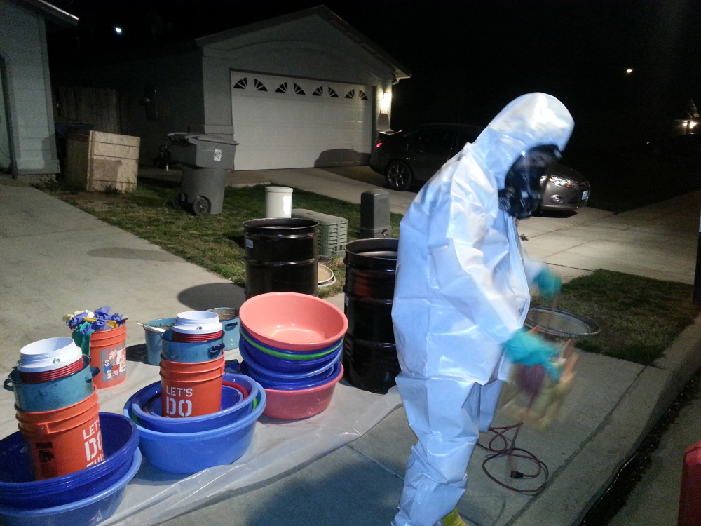 Jeff Davis, a hazardous materials specialist for PARC Environmental, cleans up a meth conversion lab inside a house in Madera, Calif. Authorities in California's Central Valley say that in recent years they have begun to see more meth dissolved as liquid and put into tequila bottles or plastic detergent containers to smuggle it across the border from Mexico.