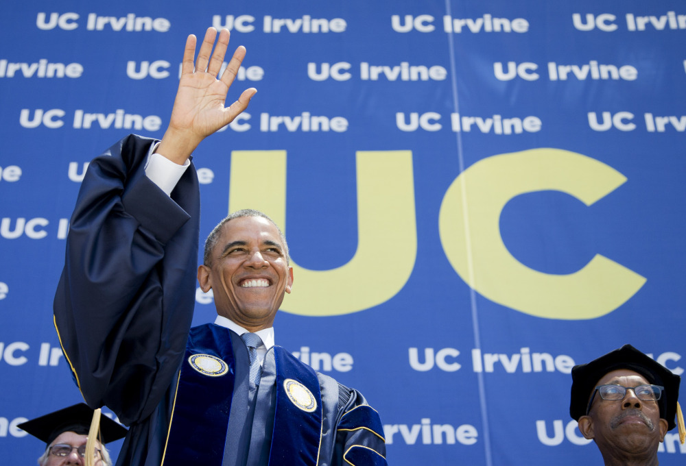 President Obama, with University of California, Irvine Chancellor Michael Drake, waves to the UCI graduating class at Angel Stadium in Anaheim, Calif., on Saturday.