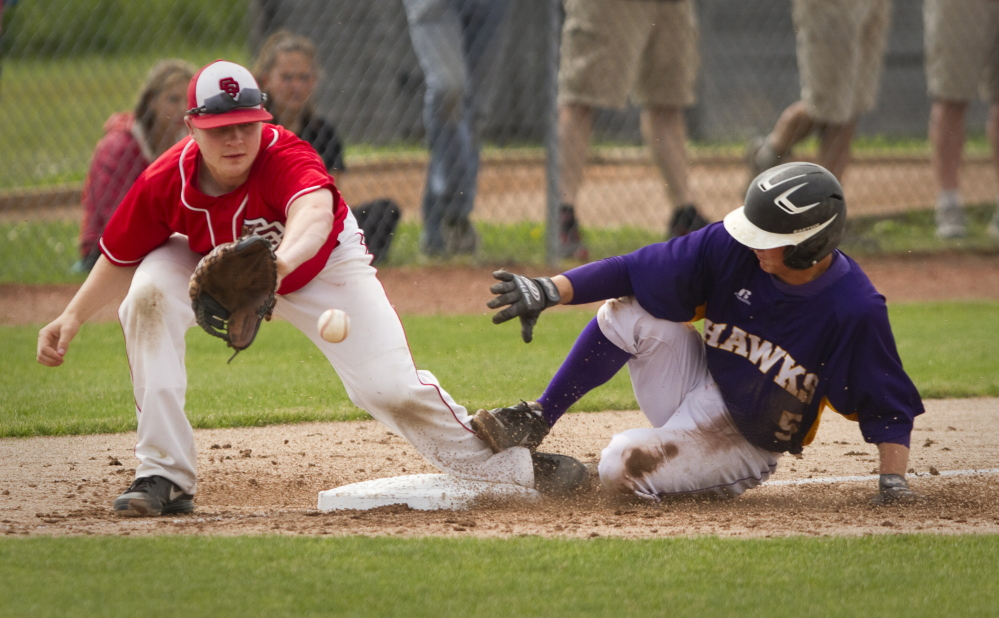 Marshwood baserunner Zachary Quintal slides safely into third as South Portland third baseman Sam Solomon tries to handle the throw  during Class A semifinal game action at the Wainwright Complex in South Portland on June 14, 2014.