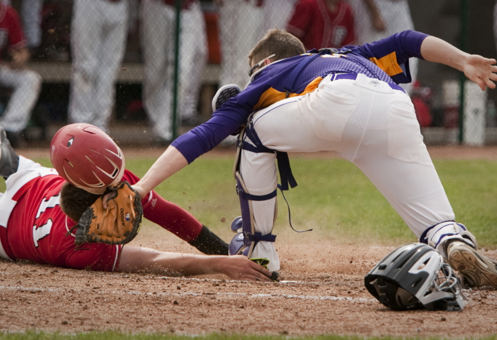 Marshwood catcher Luke Stankovich places a tag on Christopher Foley of South Portland to cut down a run in the fifth inning Saturday during Marshwood's 3-1 victory in the Western Class A semifinals at South Portland.