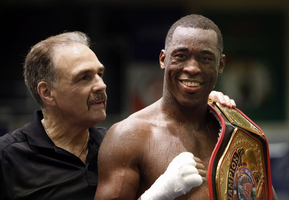 Portland Boxing Club Coach Bob Russo congratulates Russell Lamour on Saturday after he defeated Laatekwei Hammond to capture the New England middleweight championship at the Portland Expo.