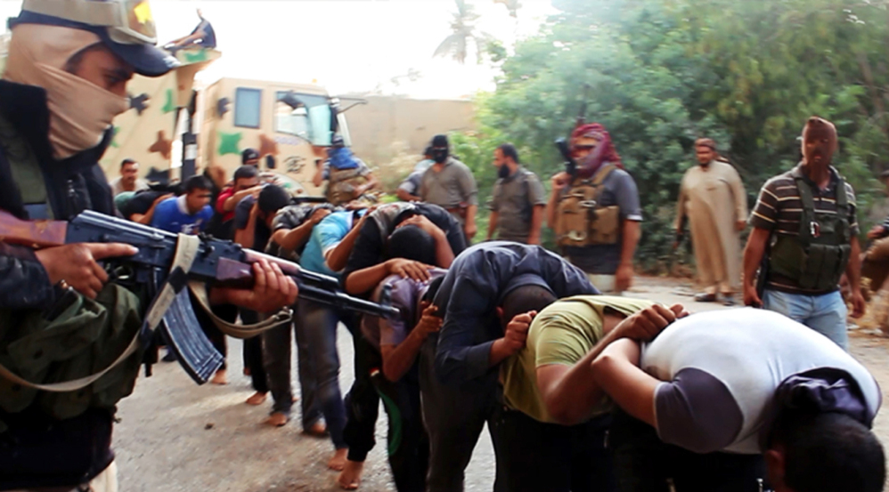 This image posted on a militant website on Saturday appears to show militants from the al-Qaida-inspired Islamic State of Iraq and the Levant (ISIL) leading away captured Iraqi soldiers dressed in plain clothes after taking over a base in Tikrit, Iraq.