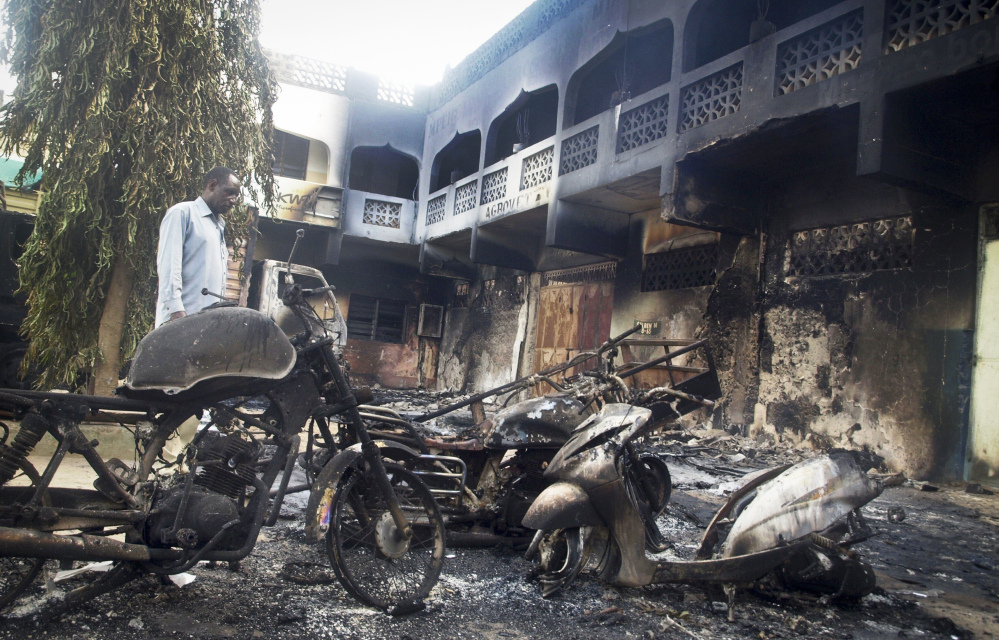 The remains of destroyed vehicles and buildings smolder in the town of Mpeketoni, about 60 miles from the Somali border on the coast of Kenya Monday. Dozens of Somali extremists wielding automatic weapons attacked the small Kenyan coastal town for hours, assaulting the police station, setting two hotels on fire, and spraying bullets into the street killing dozens, officials said Monday.