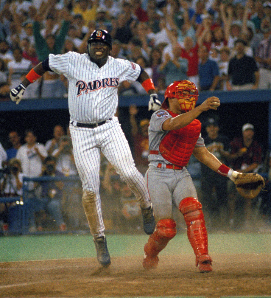 In this July 12, 1994, photo, San Diego Padres' Tony Gwynn leaps in the air after sliding home safely to score the winning run as Texas Rangers catcher Ivan Rodriguez stands by in the 10th inning of the MLB All-Star Game at Pittsburgh's Three Rivers Stadium.