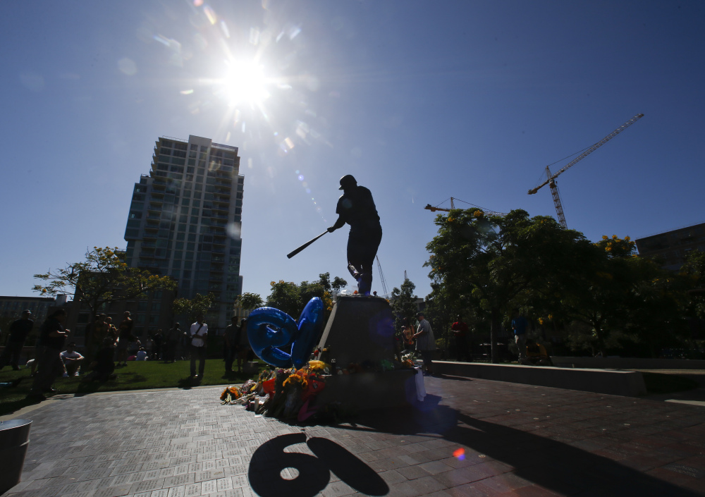 "The Tony Gwynn statue ""Mr.Padre"" is silhouetted against the late afternoon sun as his number ""19""  shines through balloons Monday, June 16, 2014, in San Diego. Gwynn, who won eight National League batting titles and was a member of the Baseball Hall of Fame, died Monday at 54 from cancer.  (AP Photo/Lenny Ignelzi)"