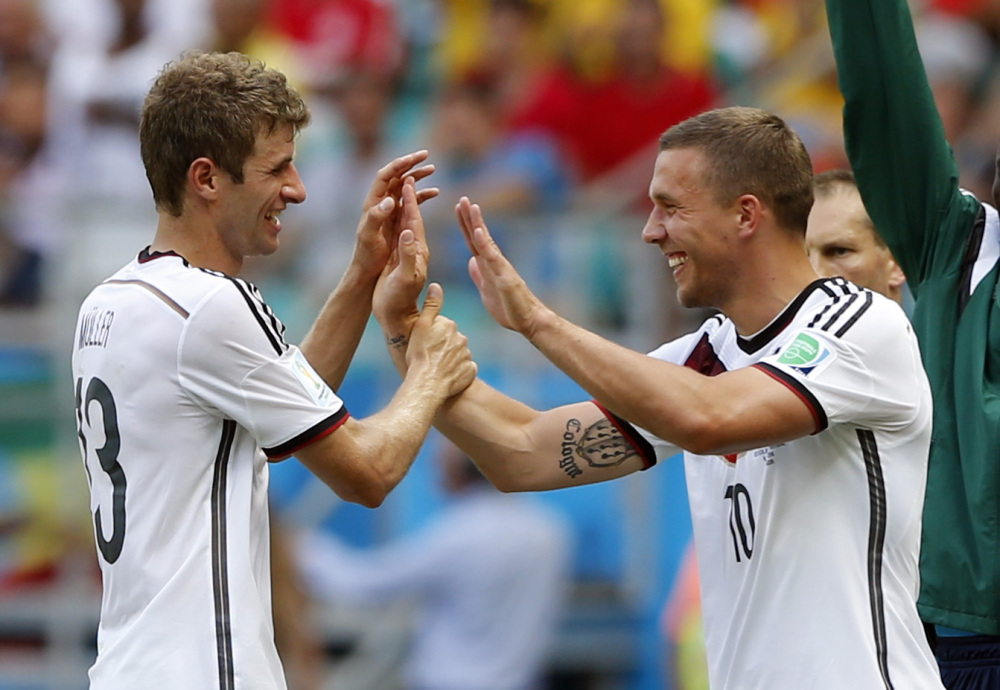 Germany's Thomas Mueller, left, is greeted by Lukas Podolski after being substituted after scoring a hat-trick during the Group G World Cup soccer match between Germany and Portugal in Salvador, Brazil, on Monday.