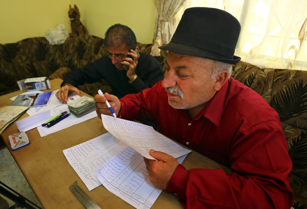 The mayor of Alqosh, Sabri Boutani, and Friar Gabriel Tooma check documents of internally displaced Iraqis to give them permission to stay in Alqosh, a village of some 6,000 inhabitants about 31 miles north of Mosul, northern Iraq.