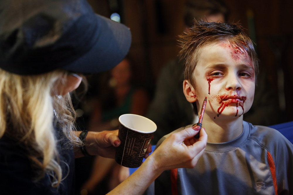 "Derek Davis/Staff Photographer Ozric Stewart, 7, of Yarmouth gets his hair and makeup done Monday before his scene in ""Night of the Living Deb."""