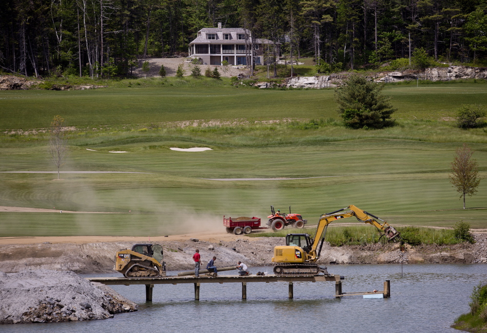 "Workers build a bridge over a pond at the Boothbay Harbor Country Club on Wednesday. A ""floating tee"" where golfers can tee off on a tiny island will be one of many new features in the redesigned golf course."