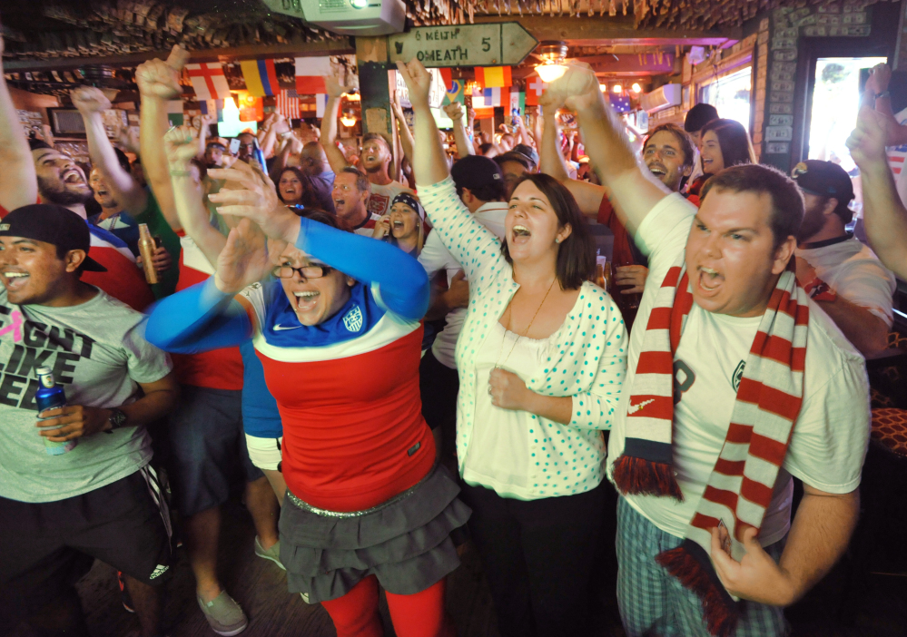Soccer fans cheer after the USA scores a goal early in their World Cup match against Ghana Monday, June 16, 2014 at Lynch's Irish Pub in Jacksonville Beach, Fla.