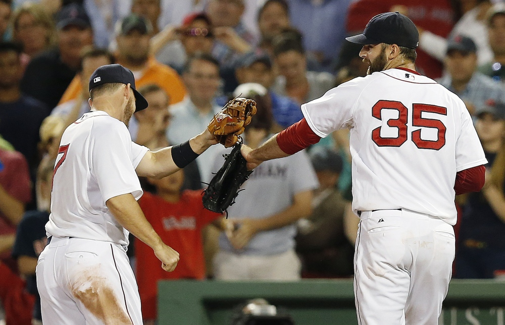 Boston Red Sox's Stephen Drew (7) taps gloves with Burke Badenhop (35) after Badenhop struck out Minnesota Twins' Brian Dozier to retire the side with bases loaded during the eighth inning Monday.