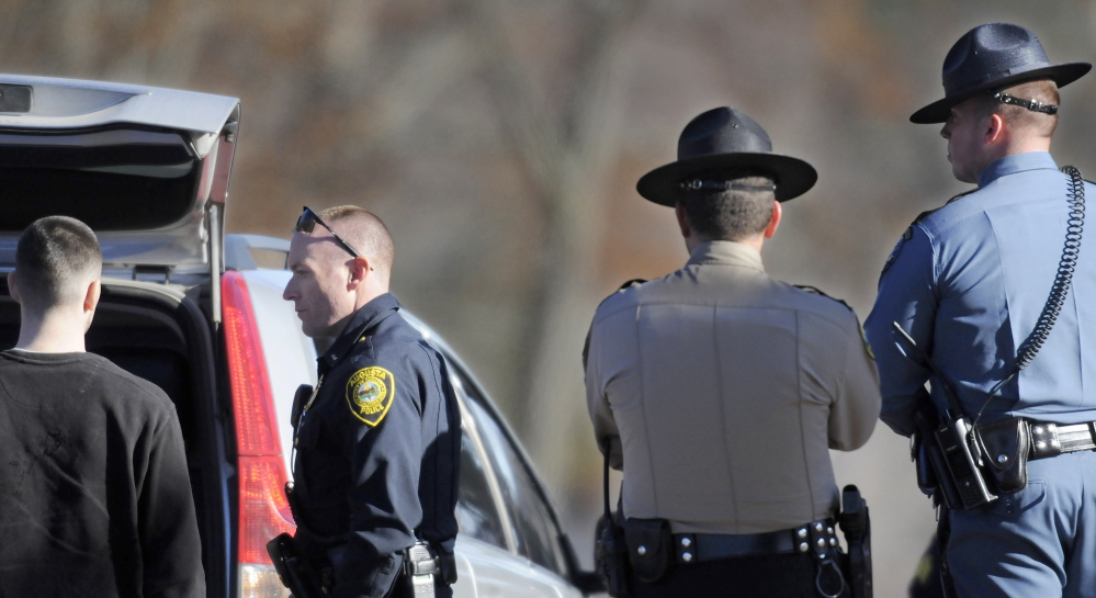 Augusta Police Lt. Kevin Lully, second from left, speaks with a man after a robbery at Shaw's in Augusta. The man was not held. The number of robberies declined in 2013.
