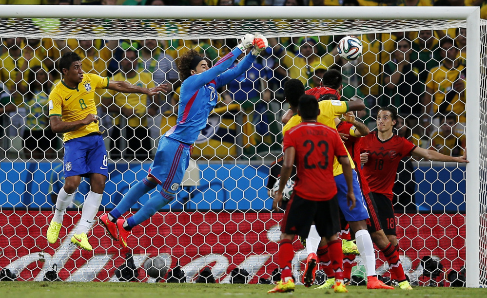 Brazil's Paulinho (8) watches as Mexico's goalkeeper Guillermo Ochoa punches the ball clear of the goal during the group A World Cup soccer match between Brazil and Mexico at the Arena Castelao in Fortaleza, Brazil, Tuesday, June 17, 2014.