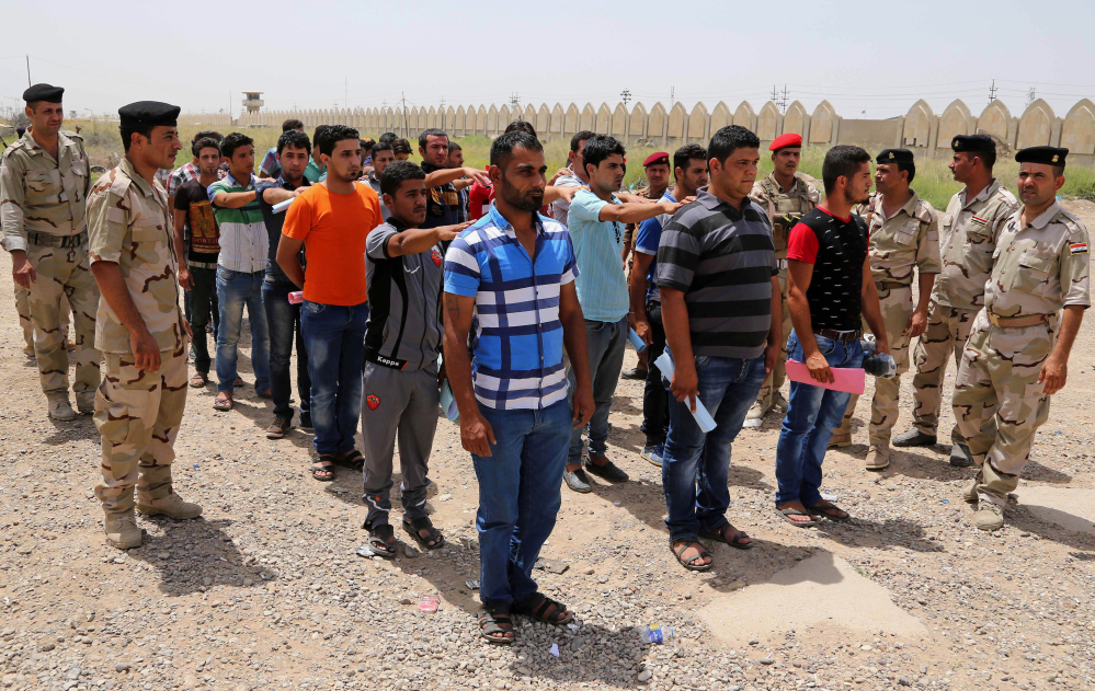 This June. 12, 2014 photo shows Iraqi men lining up outside of the main army recruiting center to volunteer for military service in Baghdad, Iraq, after authorities urged Iraqis to help battle insurgents. Iraq's military has been deeply shaken by their humiliating collapse in the face of an onslaught by Islamic militants the past two weeks.