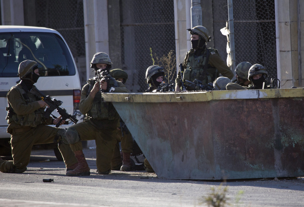 Israeli soldiers take positions Tuesday during a search for three missing Israeli teenagers in the West Bank city of Hebron.