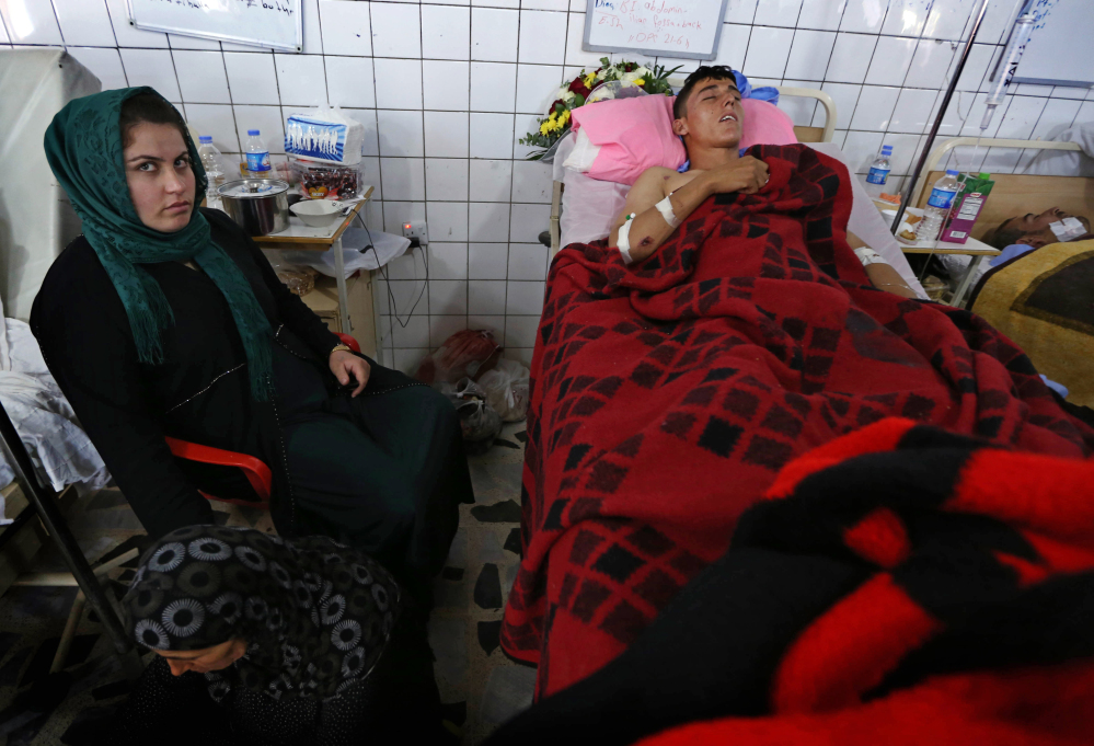Relatives stand vigil for a Kurdish peshmerga fighter wounded in fighting with al-Qaida-inspired Sunni militants as he is treated in a hospital in Irbil, Iraq, on Wednesday.