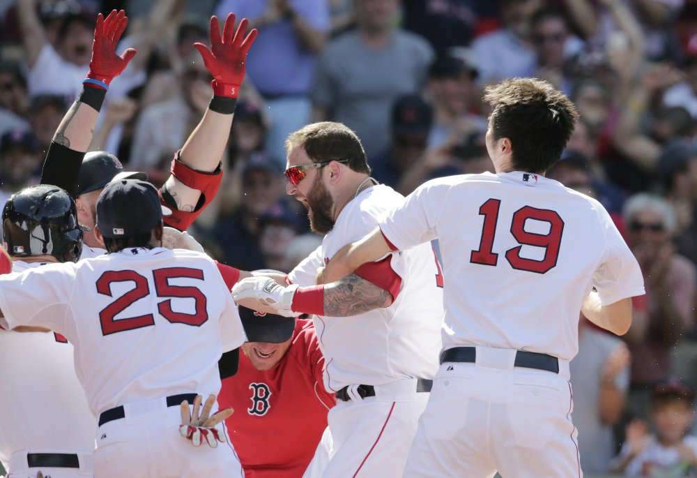 Boston Red Sox's Mike Napoli, center, is congratulated by teammates after his game-winning, walk off home run against the Minnesota Twins during the 10th inning of a baseball game at Fenway Park in Boston, Wednesday, June 18, 2014. The Red Sox won 2-1 in 10 innings.