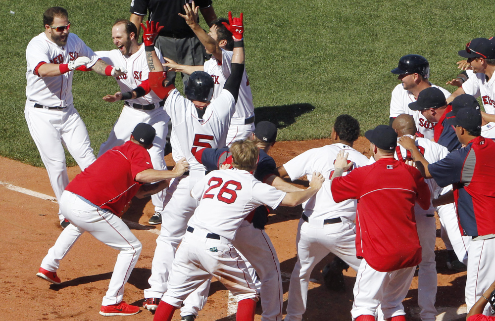 Boston Red Sox's Mike Napoli, left, is congratulated by teammates after hitting the game-winning, walk off home run against the Twins. The Red Sox won 2-1 in 10 innings.