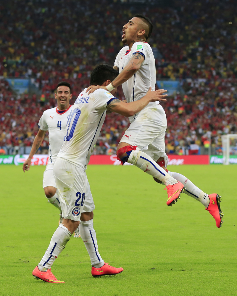 Chile's Charles Aranguiz, left, celebrates after scoring his side's second goal during the group B World Cup soccer match between Spain and Chile at the Maracana Stadium in Rio de Janeiro, Brazil, Wednesday, June 18, 2014.  (AP Photo/Bernat Armangue