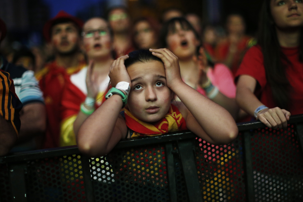 A Spanish soccer fan holds her head as she watches, on a giant display, the World Cup soccer match between Spain and Chile, in Madrid, Spain, Wednesday, June 18, 2014.