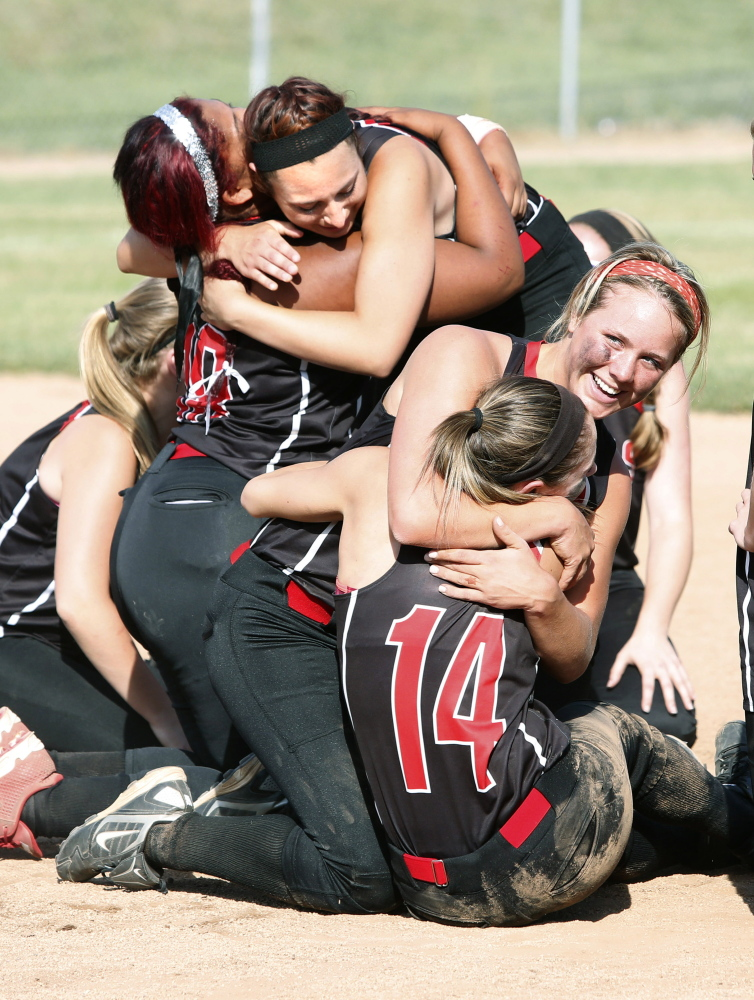 Wells High School player Lauren Bame hugs Sophie Lamb as Jordan Agger, upper left, celebrates with Nodine Webster after defeating Cape Elizabeth High School for the Western Class B championship at Saint Joseph's College in Standish on Wednesday.