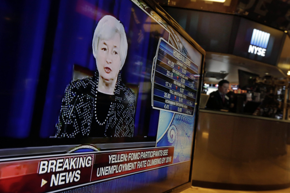Federal Reserve Chair Janet Yellen's news conference appears on a television monitor on the floor of the New York Stock Exchange, Wednesday, June 18, 2014. The Federal Reserve says it will further slow the pace of its bond purchases because a strengthening U.S. job market needs less support. But it's offering no clear signal about when it will start raising its benchmark short-term rate.