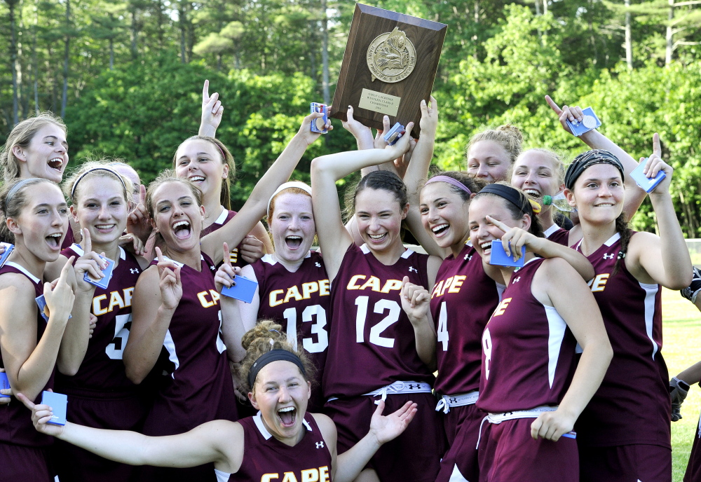 The Cape Elizabeth's girls' lacrosse team celebrates after edging Kennebunk 8-7 in overtime in the Western Class B final Wednesday at Cape Elizabeth.