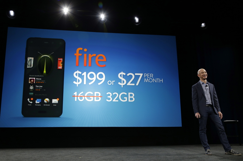 Amazon CEO Jeff Bezos stands next to an image showing the $199 price and depicting a 32GB Amazon Fire smartphone on Wednesday in Seattle.