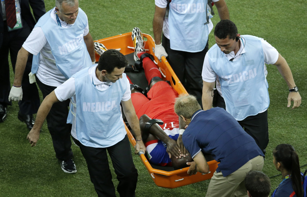 United States' Jozy Altidore is attended to by head coach Juergen Klinsmann, bottom, as he is carried off the pitch during the group G World Cup soccer match between Ghana and the United States.