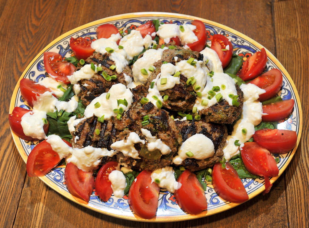 The finished dish: grilled burgers with ground lamb and ground goat meat, fresh mint and grated onion on a bed of sliced tomatoes and wilted spinach and garnished with chopped green garlic. The white sauce is made from sheep milk yogurt mixed with goat milk feta cheese. Gordon Chibroski/Staff Photographer