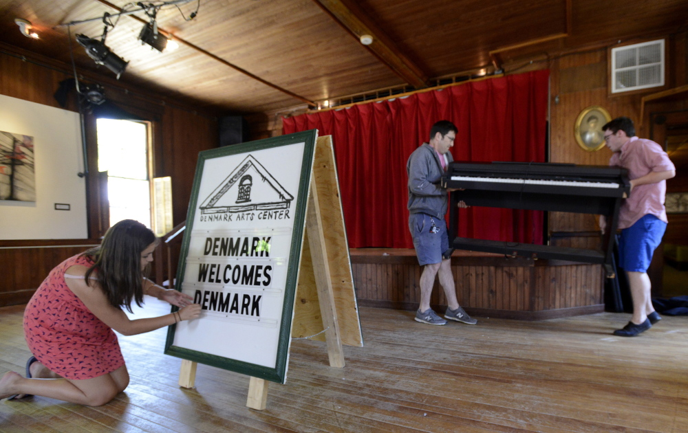 Catie Gillette prepares a sign Thursday while Jamie Hook and Harrison Corthell lift an electronic piano on stage as they get the town of Denmark ready for Saturday's goodwill concert sponsored by the Consulate General of Denmark in New York City.