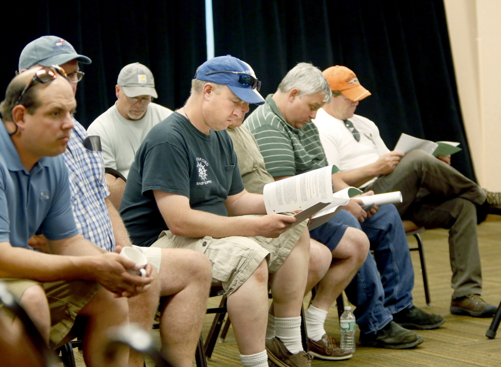 Herring fishermen from Rockland look over informational material during the New England Fishery Management Council meeting at the Holiday Inn by the Bay in Portland. The council voted 10-0 against raising the limit on haddock bycatch to help the herring fleet.