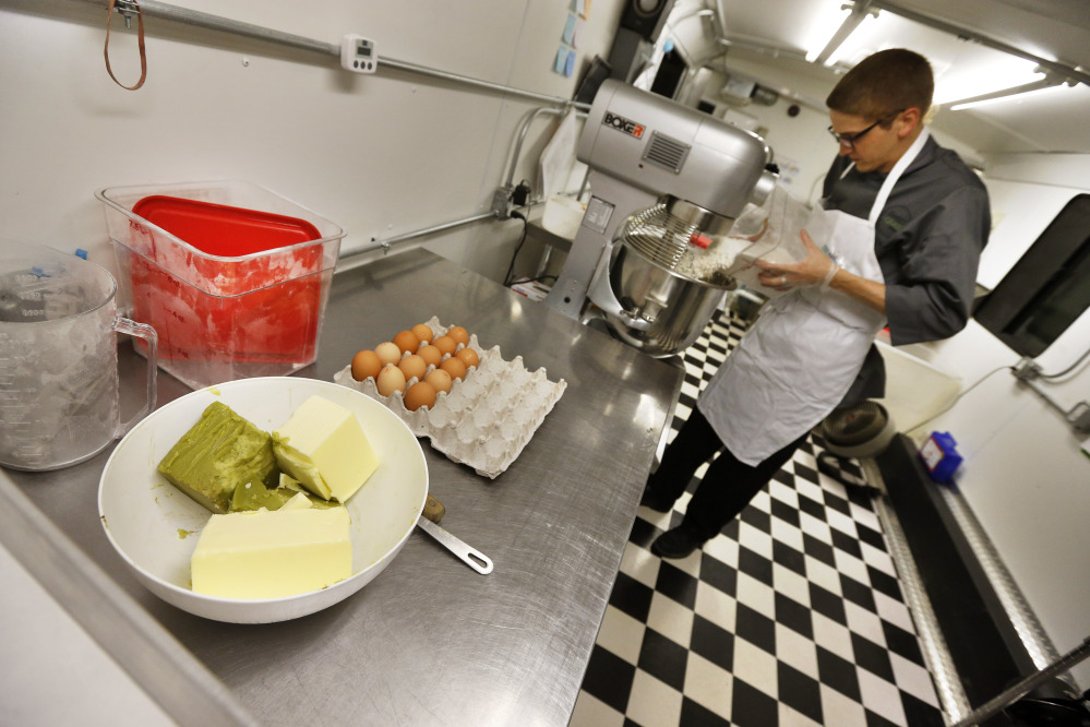 "Chef Alex Tretter prepares a batter for peanut butter and jelly cups, with green cannabis-infused ""canna butter"" in a bowl at left, at Sweet Grass Kitchen, a gourmet marijuana edibles bakery that sells its confections to retail outlets, in Denver."