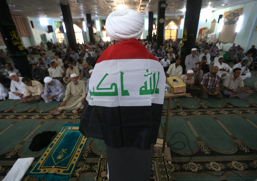 A Shiite cleric, his back covered by an Iraqi flag, prays Friday at a Shiite mosque in the northern oil-rich province of Kirkuk, Iraq.