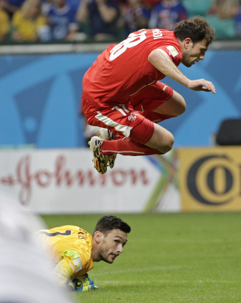 Switzerland's Admir Mehmedi leaps over France's goalkeeper Hugo Lloris after taking a shot on goal during the group E World Cup soccer match between Switzerland and France in Salvador, Brazil, on Friday.