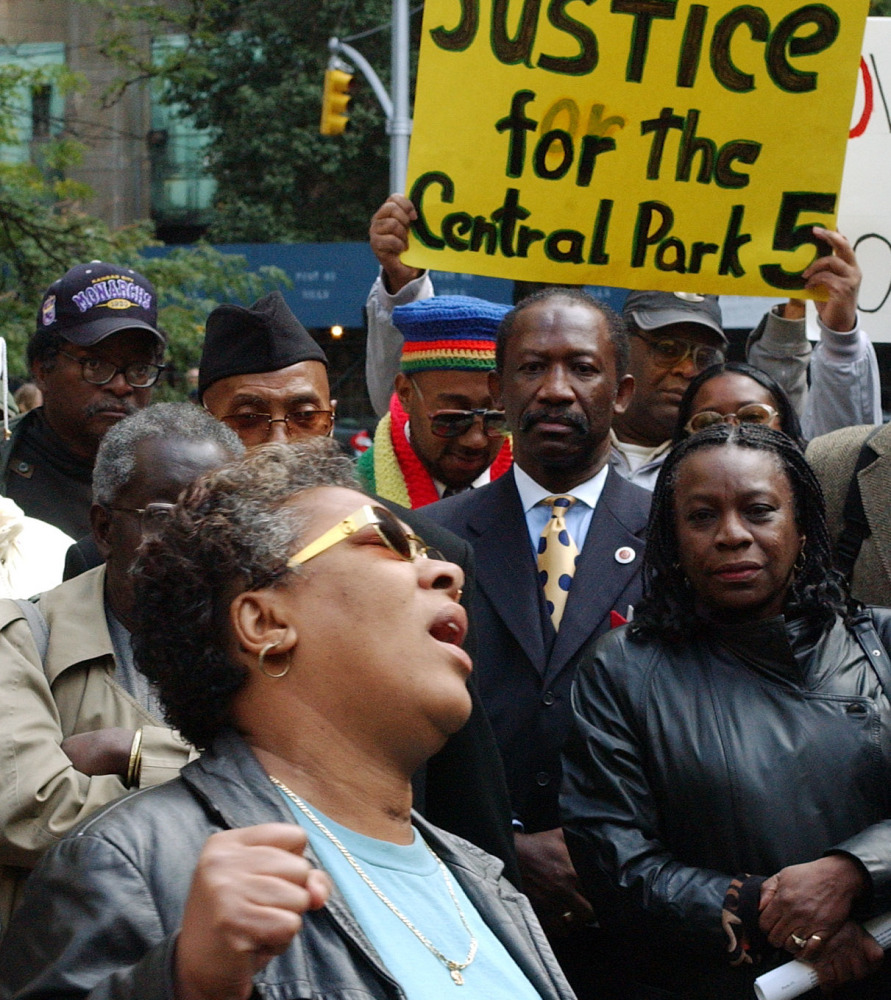 "Dolores Wise, left, whose son Korey Wise was one of five youths convicted in the 1989 Central Park jogger case, sings ""We Shall Overcome"" at a 2002 rally in New York City. The city has settled a civil rights lawsuit by the five men exonerated in the case."