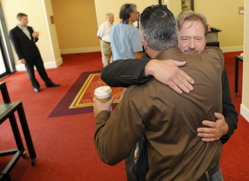 Frank Schaefer, right, a United Methodist Church pastor who was defrocked for officiating at his son's same-sex wedding, hugs supporter Ben Overturf of Harrisburg, Pa., before a Methodist judicial panel heard the appeal of Schaefer's defrocking Friday in Linthicum, Md.