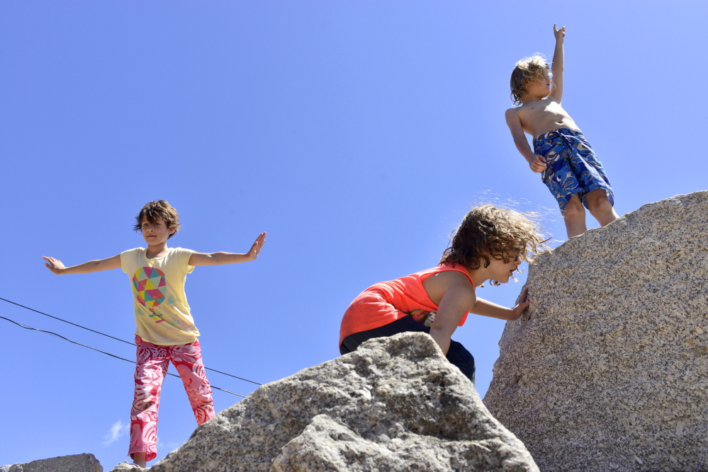 "From left, Maiya Koloski, Chloe Koloski and Everrett Calhoun climb the rock formations at Nason's Corner Park in Portland on Thursday. ""Saturday in the Park"" will be held from 10 a.m. to 1 p.m. and will include a yoga class, pancake breakfast, face painting and raffles."