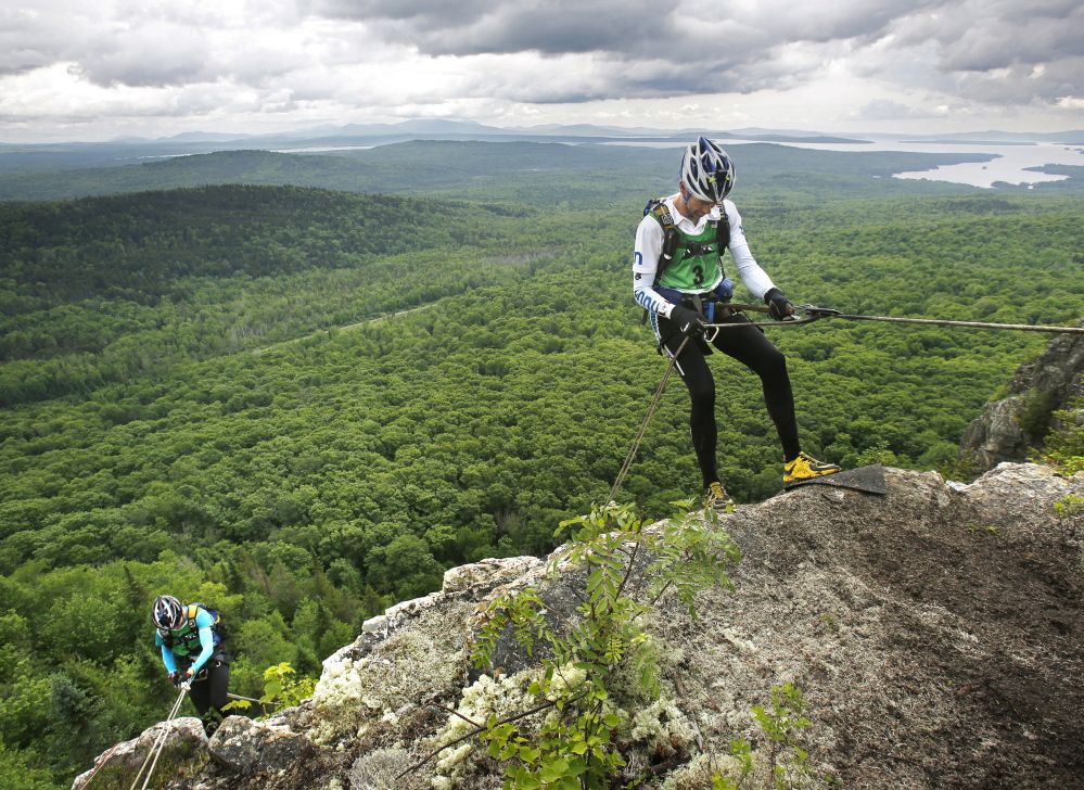 It's not all downhill from here, but on the first day of the 200-mile, four-day wilderness adventure in the Moosehead Lake region, Ryan VanGorder, right, of team Dart Nuun began his rappel down Little Kineo Mountain, where other grueling tests were waiting at the base.