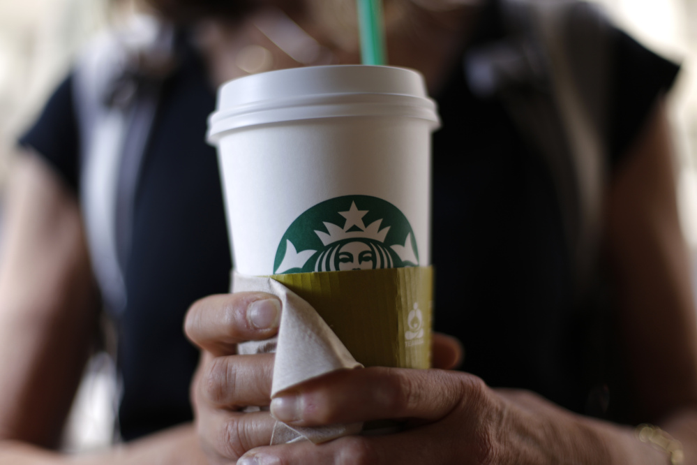 A woman holds a coffee drink outside a Starbucks in downtown Chicago. Starbucks is raising prices on some of its drinks by 5 cents to 20 cents starting next week, and customers can soon expect to pay $1 more for the packaged coffee it sells in supermarkets. Prices for medium and large brewed coffees, which are known as Grande and Venti, respectively, will go up between 10 cents and 15 cents in most U.S. markets, the company said.