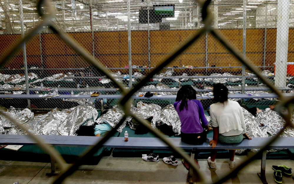 Two girls watch a World Cup soccer match on a television with other children lying under reflective blankets on Wednesday in their holding area at the U.S. Customs and Border Protection Nogales Placement Center in Nogales, Ariz.